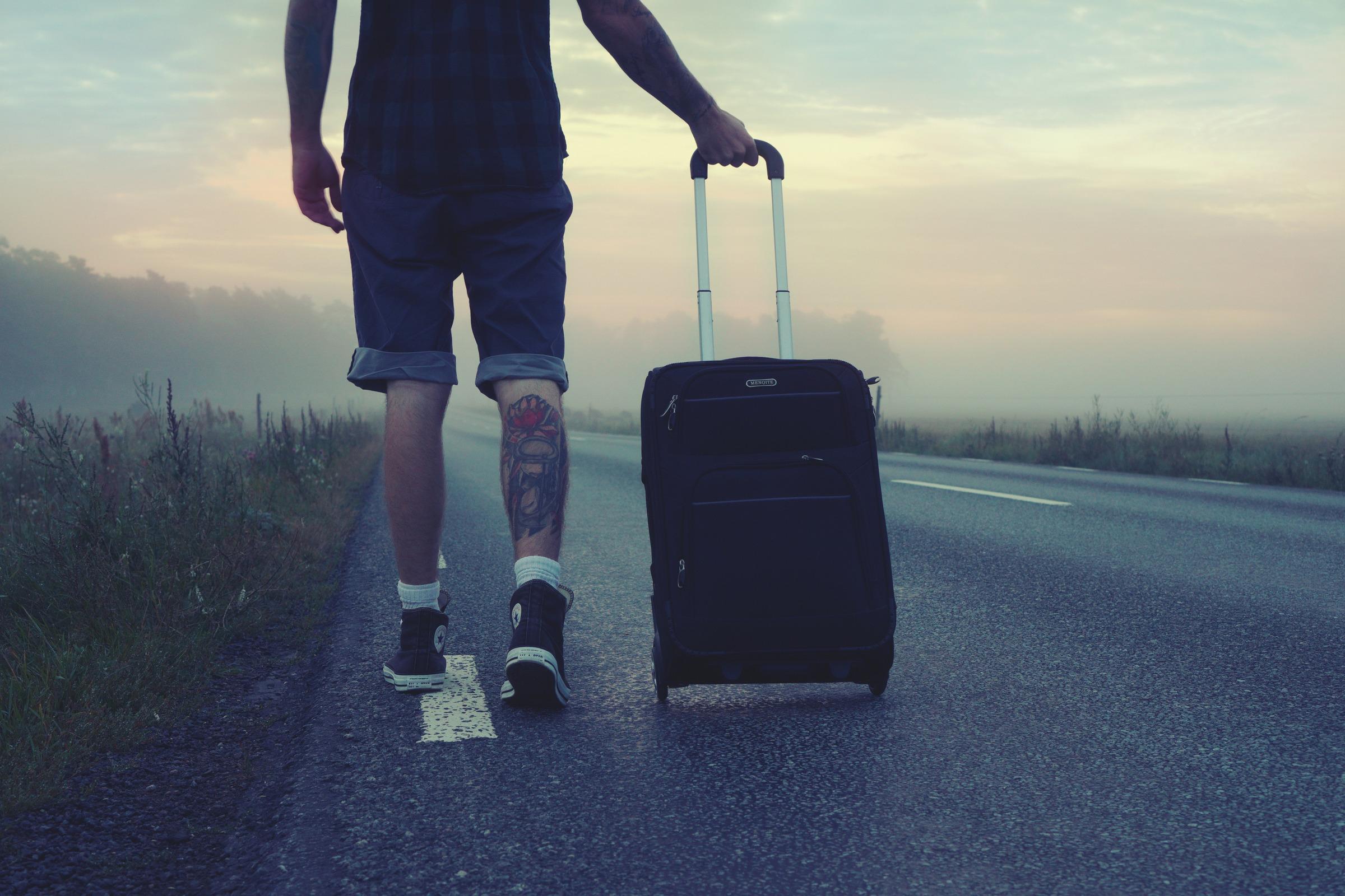 Hombre camina con una maleta, vista posterior de sus piernas