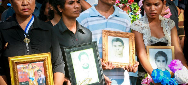 Familiares seguram fotos de pessoas desaparecidas